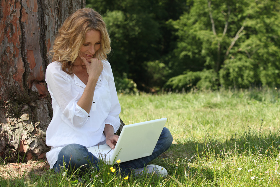 Blond woman sat by tree with laptop